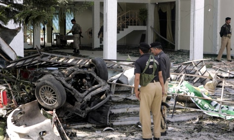 Image: Pakistani police officers examine the wreckage of a car