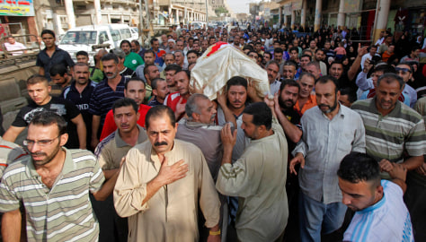 Image: Mourners carry the coffin a victim