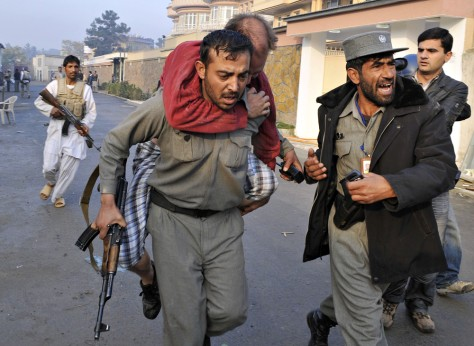 Image: An injured man is carried by police
