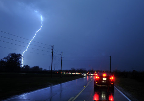Image: Lightning strikes as a very long line of cars creep down West Swan Lake Road
