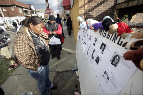 Image: Neighbors Tee Johnson, left, and Cordell Solomon, right, look at a make-shift memorial