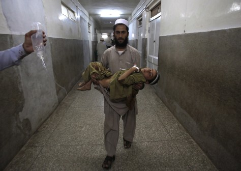 Image: A father carries his injured son through the halls of a hospital