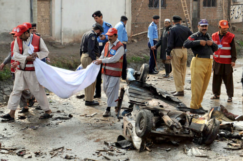 Image: Rescue workers clean up wreckage after a suicide bombing