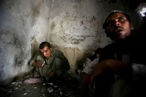 Image: Opium addicts squat on the floor