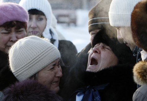 Image: The mother of nightclub fire victim is comforted by relatives during a burial ceremony at a cemetery outside Perm
