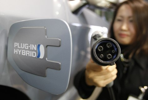 "Image: Toyota Motor Corp. staff demonstrates how to recharge ""Prius Plug-in Hybrid"" car at its showroom in Tokyo"