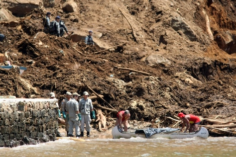 Image: Rescue workers carry a landslide victim's body