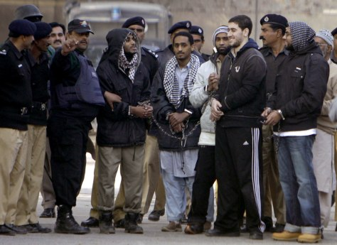 Image: Pakistani policeman escorts American men after their court appearance in Sargodha
