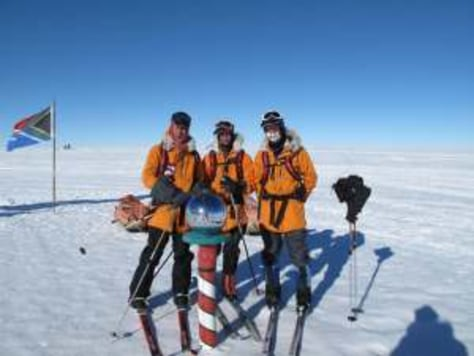 Image: Trekkers at ceremonial South Pole marker