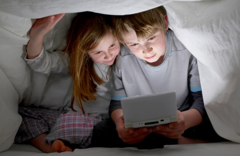 Image: Kids play video games under a sheet