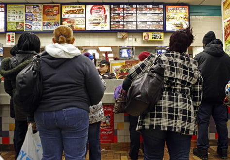 Image: People line up to buy food at a fast food restaurant in Harlem in New York