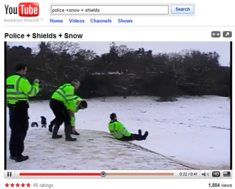 Image: Youtube.com video showing a police officer sledding on a riot shield.