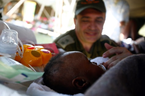 Image: Avi Berman, of Israel, sits next to a baby that was rescued from the collapsed house