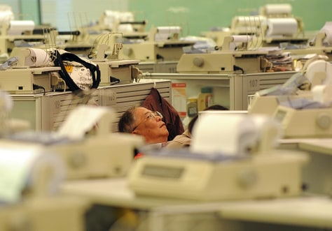 Image: A trader works at the Stock Exchange in Hong Kong