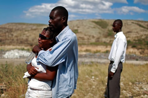 Image: People react during a memorial service in Haiti