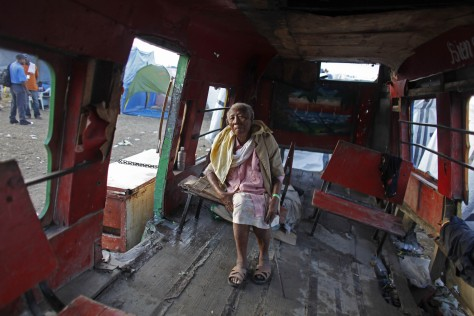 Image: Dieudone Bernard, 87, sits in a damaged public bus