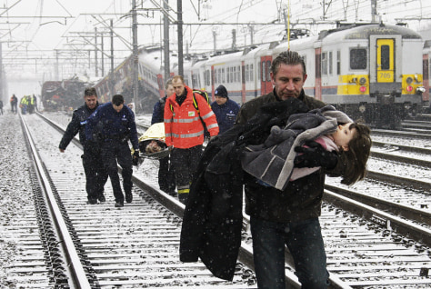 Image: A man carries a child from site of train crash in Belgium