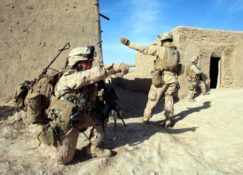 Image: U.S. Marines from Bravo Company of the 1st Battalion, 6th Marines, gesture during an operation in the town of Marjah