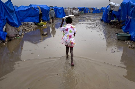 Image: Girl walks through flooded survivors camp in Haiti