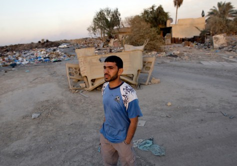 Image: A man walks past a wreckage of an Iraqi military vehicle in Baghdad