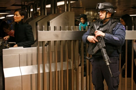 Image: A counterterrorism officer stationed at Grand Central Station in New York keeps his eye on commuters at subway turnstiles