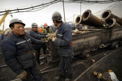 Image: Mine workers prepare to send equipment down the entrance to the Wangjialing coal mine