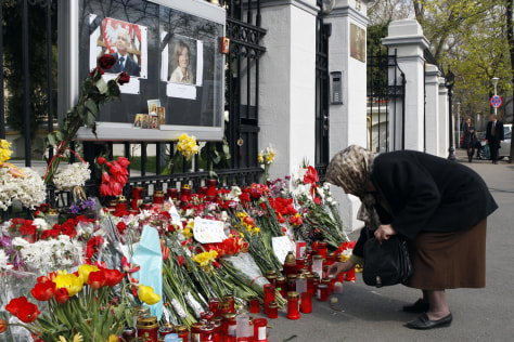 Image: A woman lights a candle in front of the Polish Embassy in Bucharest.