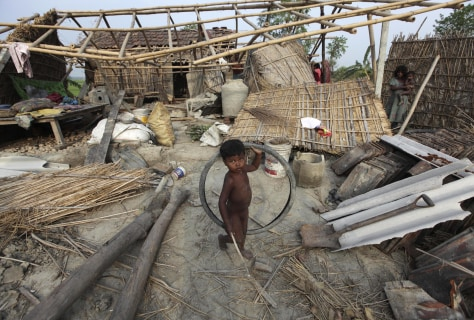 Image: A boy holds a bicycle tyre in front of damaged huts