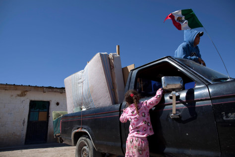 Image: A family leaves their home in Guadalupe after drug cartel members threat residents