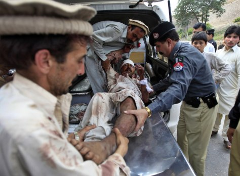 Image: Relatives and a policeman assist a man who was injured in a suicide attack in a village of Kacha Pakha near Kohat