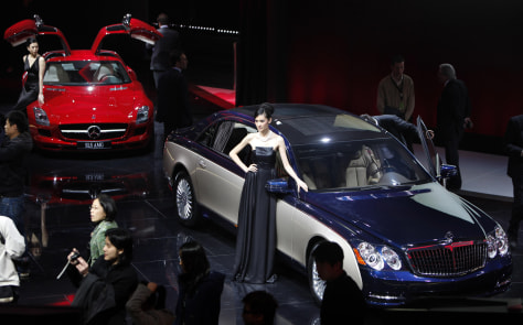 Image: Models stand next to a Daimler Maybach, right and Mercedes-Benz SLS