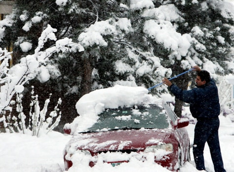 Image: Heriberto Perez Rios clears his car of snow