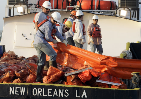 Image: Workers load oil booms onto a crew boat