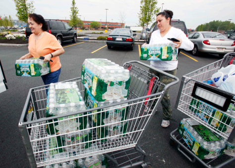 Image: Enelcy Scott, left, and Diana Cardona, both of Boston, load bottled water into their car outside a supermarket in Chelsea, Mass.