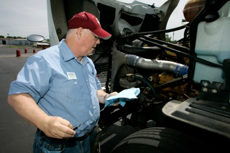 Image: Student Tommy Wood checks the oil in a training truck at Central Tech Truck Driver Training in Drumright, Okla.