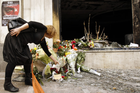 Image: A woman puts flowers in front of the bank branch where three people were killed in Athens