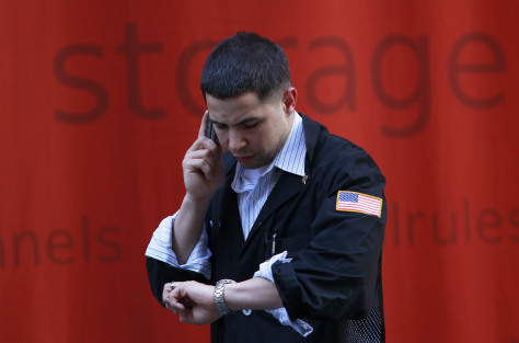 Image: A trader talks on his phone outside of the NYSE.
