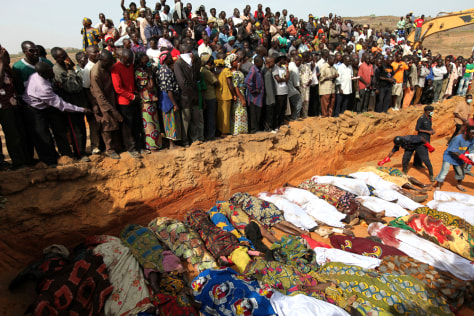 Image: Villagers look at bodies of victims of religious attacks lying in a mass grave in the Dogo Nahawa village