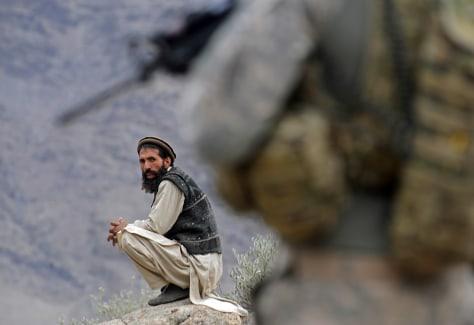 Image: An afghan man looks on as a U.S. soldier patrols