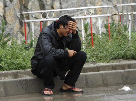 Image: A man grieves outside the airport terminal in Kabul