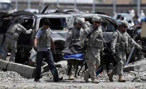 Image: U.S. soldiers carry a body at the site of a suicide car bombing in Kabul