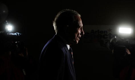 Image: Sen. Specter walks past television cameras following a news conference in Philadelphia