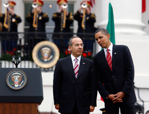Image: U.S. President Obama and Mexican President Calderon talk during the official arrival ceremony at the White House in Washington