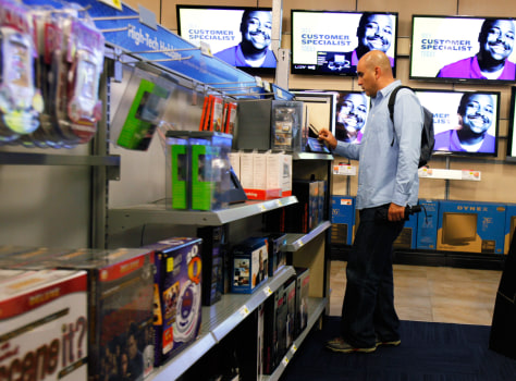 A man shops for electronics at a Best Buy store in New York. Economists forecast the pace of U.S. growth to pick up in the year ahead.