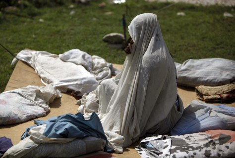 Image: A woman sits on a cardboard at a camp in Port-au-Prince