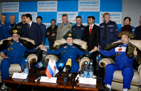 Image: Creamer, Kotov and Noguchi sit in Kazakh national costumes at a news conference in Karaganda airport