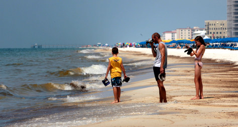 Image: Dale Scheidemantle, center, and his children Josiah, left, and Faith walk near the oily surf in Orange Beach, Ala.