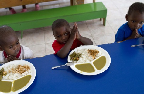 Image: 3-year-old Sonson, center, prays with other children before eating at an orphanage on the outskirts of Port-au-Prince.