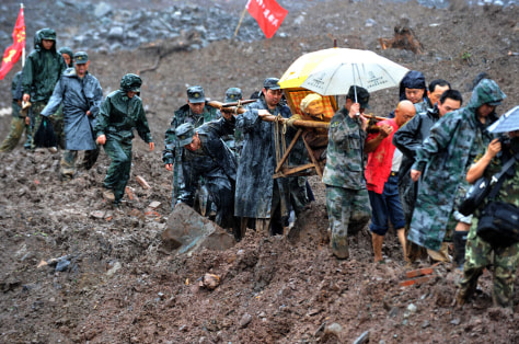 Image: Chinese soldiers evacuate residents from the site of a landslide