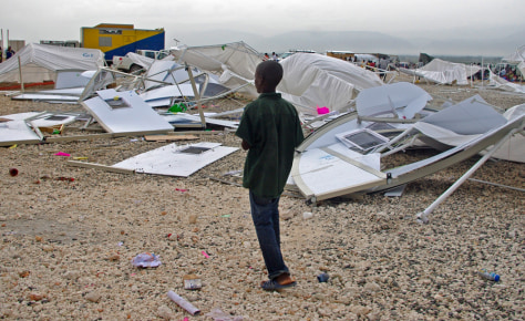 Image: A boy walks in front of a structure that collapsed due to heavy rain at the Corail refugee camp